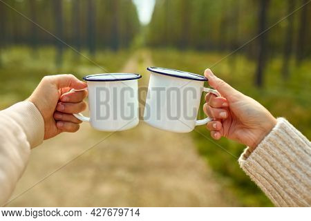 picking season, leisure and people concept - hands of man and woman clinking white tin tea mugs in forest