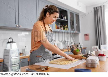 culinary, bake and people concept - happy smiling young woman cooking food on kitchen at home spreading dough on baking paper