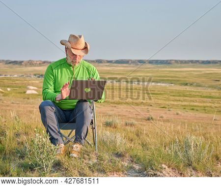 Senior man in cowboy hat is working on laptop in the middle of nowhere, early morning in Pawnee National Grassland in Colorado
