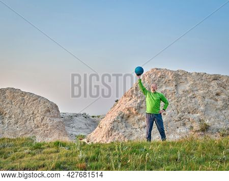 sunrise workout with a heavy slam ball - senior man ix exercising in Pawnee National Grassland in Colorado
