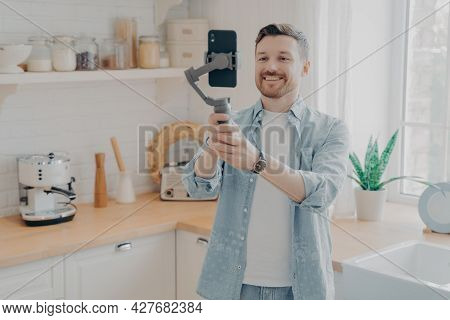 Young Man Blogger Recording Video Blog Or Live Streaming With Smartphone And Gimbal Indoors Standing