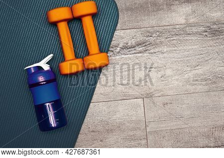 Colorful Bright Fitness Stuff Is Scattered On The Gym Floor. Dumbbell, Sports Mat, And Bottle. Bodyc