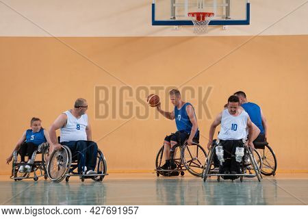 Disabled War veterans mixed race opposing basketball teams in wheelchairs photographed in action while playing an important match in a modern hall.