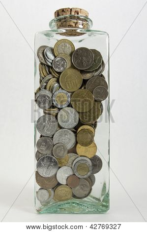 A glass jar filled with coins