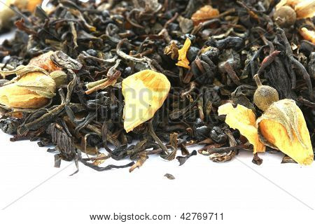 Dry black tea flavored with dry flower buds on white background