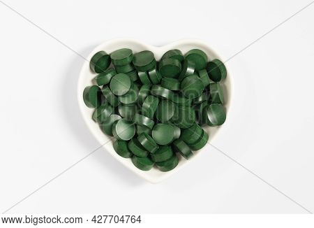 Spirulina Green Pills In A Heart Plate Isolated On A White Background. Natural Supplement Made From