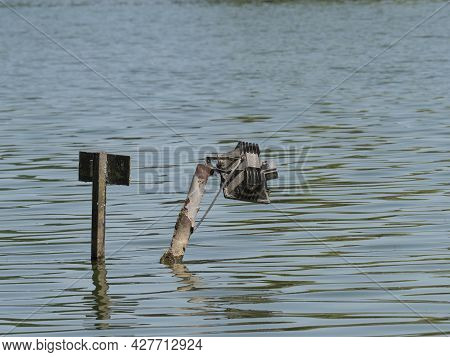 Broken Lamp Stands In The Water With An Exposed Electricity Cable