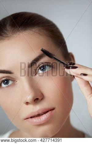 Young Beautiful Woman Correcting Shape Of Eyebrows. Contouring Eyebrow Makeup .