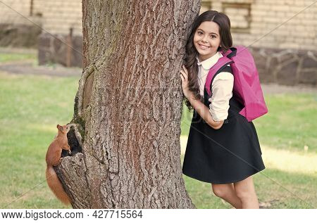 Happy Small Kid In Uniform With School Backpack Resarch Squirrel Climbing Tree In Park, Zoology.