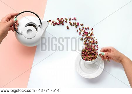 Dry Rose Flower Herbal Tea. Surreal Flat Lay With Dried Rose Flowers Pouring From White Ceramic Tea