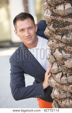 Hombre posando detrás de un árbol