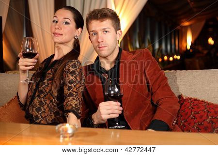 man and woman with a glass of wine watching the camera