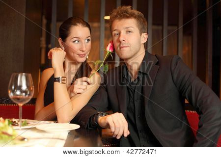 woman holds in her hand a flower and flirting with young man, focus on woman