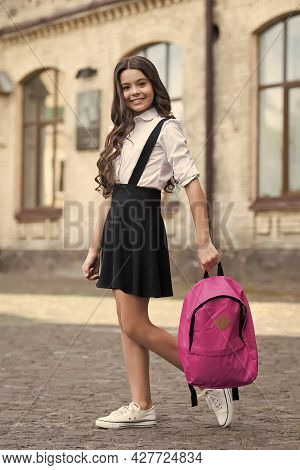 Wear The Best. Happy Child Carry Bag Outdoors. Fashion Look Of Little Schoolgirl. Formal Education.