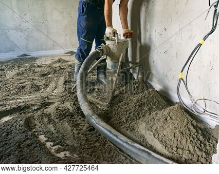 Worker At A Construction Site Screed Floor. Leveling Semi-dry Floor Screed