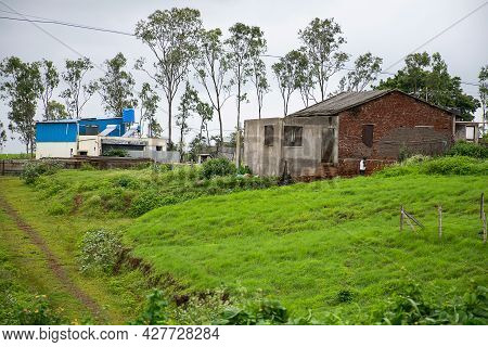 Stock Photo Of A House Constructed With Red Bricks In Between Green Grass And Trees, Blue Color Shel