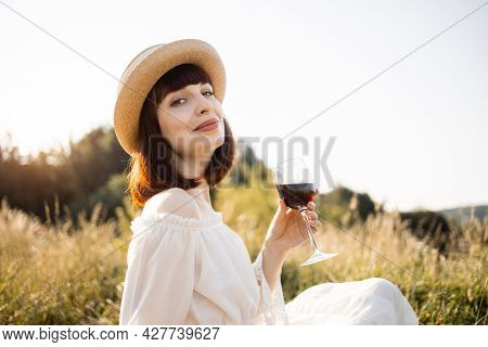 Summer Picnic And Relaxation On Sunny Day. Stunning Pretty Woman In White Dress And Hat Sitting On P