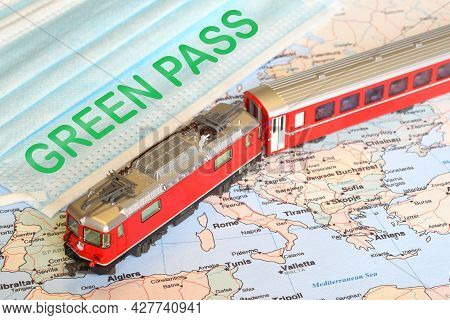 Surgìcal Masks With Text Green Pass Over A Geographical Map And A Model Of Red Train. Safe Travel Co