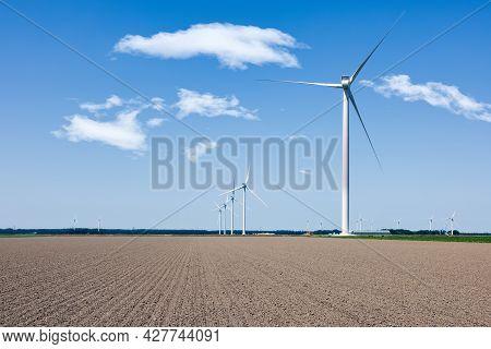 Dutch Farmland With Wind Turbine Farm Near Village Zeewolde