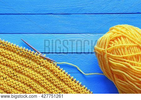 Hobbies And Knitting Concept.  Yellow Knitted Cloth With Knitting Needles On  Blue Rustic Table. Cop