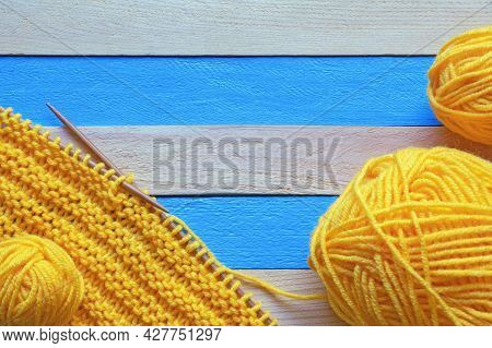 Hobbies And Knitting Concept.  Knitted Cloth With Knitting Needles And Skeins Of Wool On  Rustic Tab