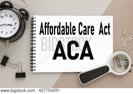 Affordable Care Act Aca, Notepad On A Background Of Different Colors. Brown, Gray. Paper Clips Are B