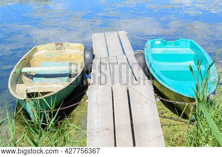 Old Fishing Boats On The Lake Are Chained. Wooden Boat Dock. Summer Sunny Day.