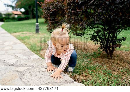 Little Girl Squatting On Green Grass In A Park Near A Paved Path
