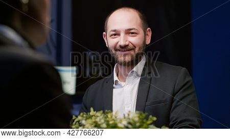 Portrait Of Focused Manager Looking Into Camera Sitting At Conference Table In Meeting Office Room L