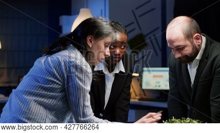 Diverse Businesspeople Coworkers Standing At Conference Table Analyzing Financial Graphs Paperwork L