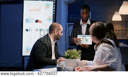 Focused African American Businesswoman Showing Company Graphs On Tablet Working In Office Meeting Ro