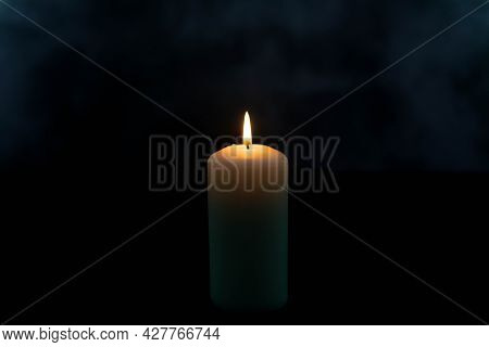 A White Candle Burning In The Dark, On A Black Background.\na Candle Made Of White Wax. It Is Placed