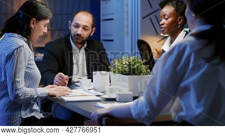 Diverse Businesspeople Discussing Management Company Solution Sitting At Conference Table In Office