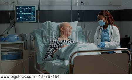 African American Medic Talking To Sick Patient In Hospital Ward With Nasal Oxygen Tube And Pulse Rat
