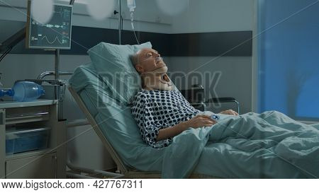 Old Patient With Cervical Neck Collar Laying In Hospital Ward Bed At Medical Facility. Sick Elder Ma