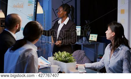 Workaholic African American Leader Standing In Front Of Presentation Monitor Explaining Marketing Pr