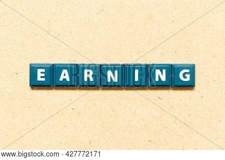Tile Alphabet Letter In Word Earning On Wood Background