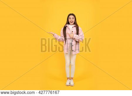 Surprised Girl In Shirt. Hipster Kid Casual Style. Tween Child In Plaid Shirt Presenting Product