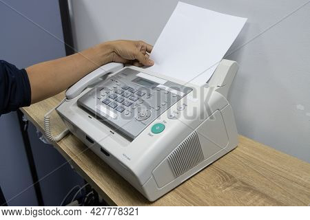 Hand Man Are Using A Fax Machine In The Office, Equipment For Data Transmission.