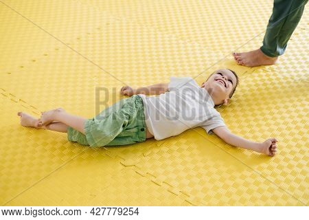 Happy Child On The Mat In Child Rehabilitation Center. Boy With Cerebral Palsy Smiling. Rehabilitati
