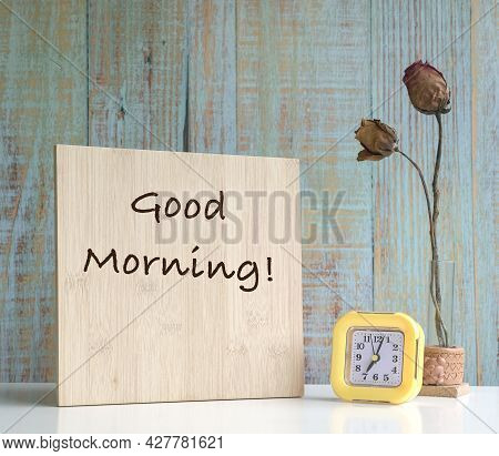 Wood Board With The Text Good Morning With Clock And Dried Flowers In Vase On Table. Blue Wood Textu