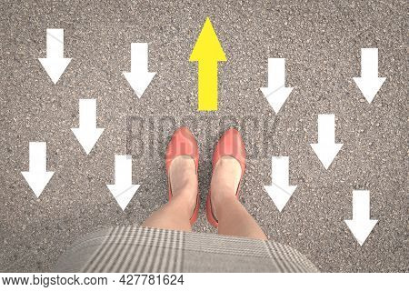 Businesswoman Standing With Orange Shoes On Street With One Yellow Arrow Against Other Opposing Dire