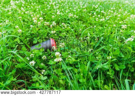 A Black Paper Coffee Cup With A Green Straw Is Thrown Into The Green Grass. Environmental Pollution