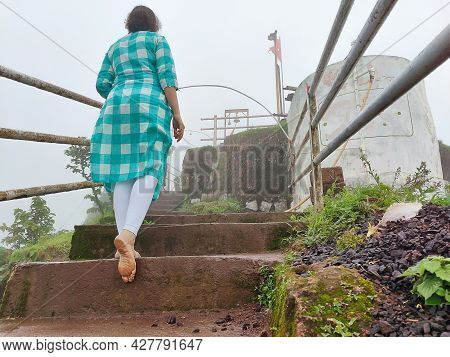 Back View Of A 20-25 Years Old Indian Girl Wearing Blue Color Top And White Leggings Climbing Wet St