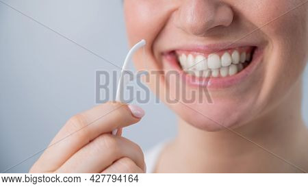 Close-up Portrait Of A Beautiful Caucasian Woman With A Flawless Smile Holding A Toothpick With Dent