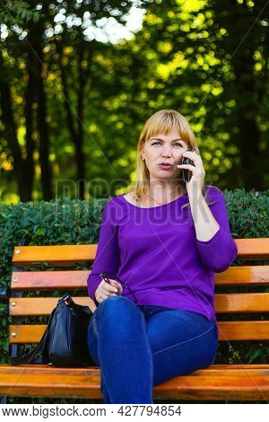 Defocus Serious Caucasian Blond Woman Talking, Speaking On The Phone Outside, Outdoor. 40s Years Old