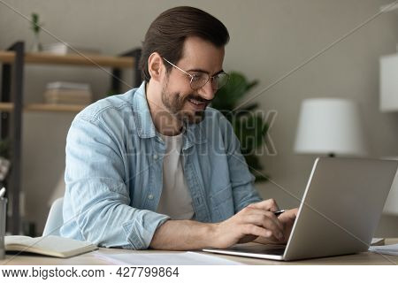 Man Sit At Desk Texting On Laptop Working From Homeoffice