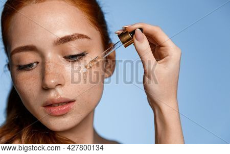 Beautiful Young Woman Apply Moisturizing Facial Serum Isolated On Blue Background. Morning Daily Bea