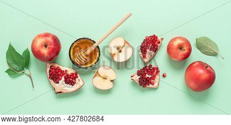 Rosh Hashanah. Jewish New Year. Apples, Pomegranate And Honey Border On Pastel Green Paper Backgroun