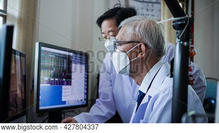 Asian Senior Elder Doctors Wearing Mask Looking At Computer Screen Diagnose Patient Data And Informa